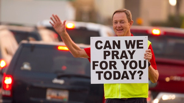 Man waving holding a can we pray for you today sign in front of cars