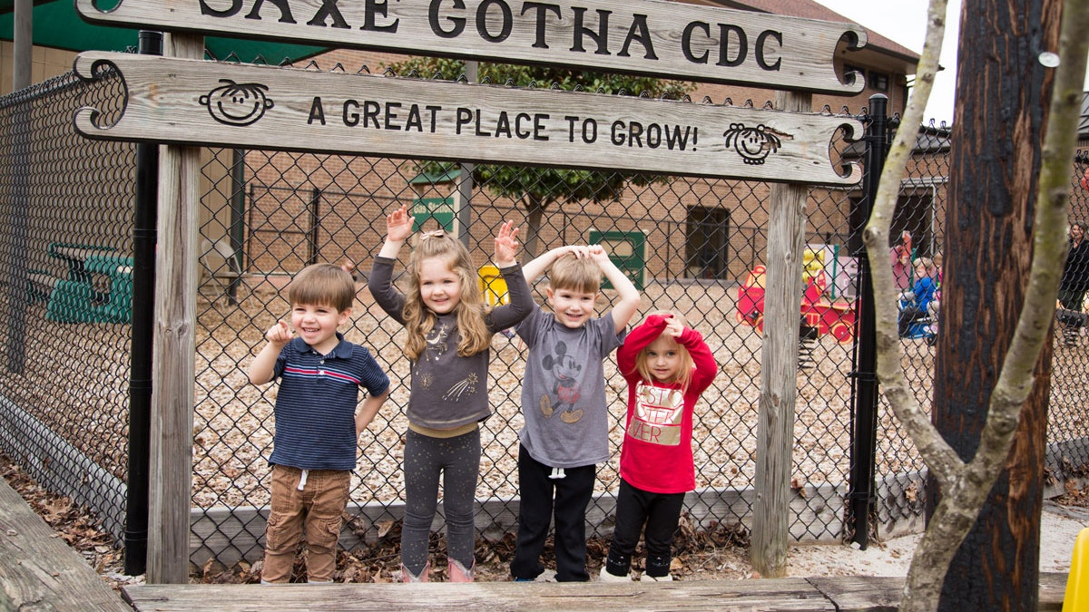 Kids standing in front of the Saxe Gotha CDC wooden sign