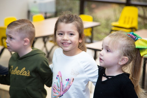 Three kids at CDC with one girl looking at the camera and smiling